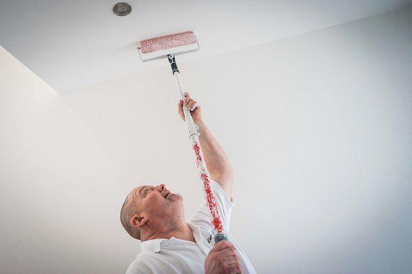 Een schilder die het plafond schildert